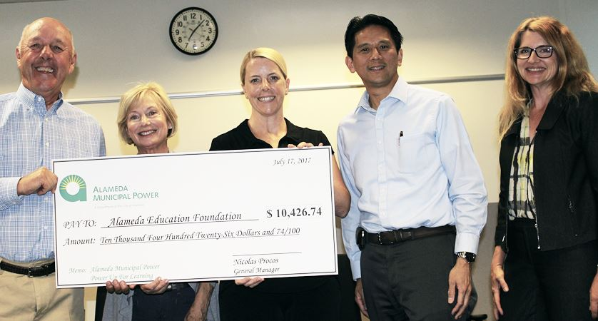 Alameda Education Foundation employees holding a donation check.