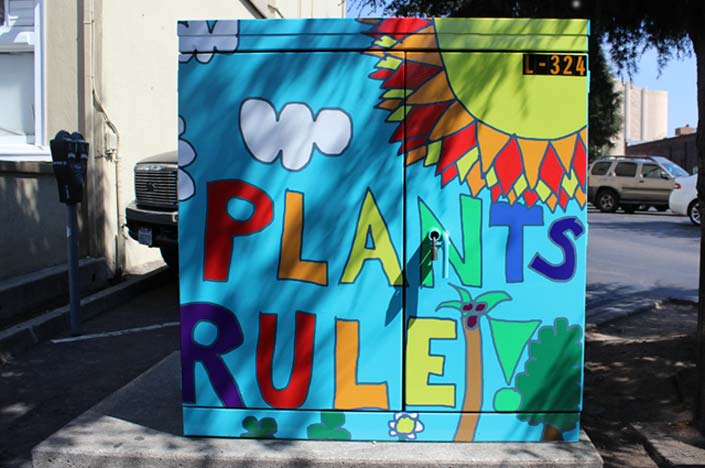 A power box painted with a sun and the words plants rule.