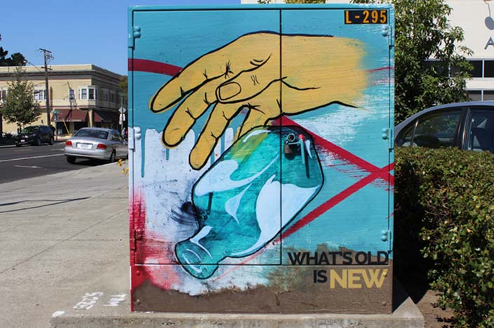 A power box with the painting of a hand dropping a glass bottle on it.
